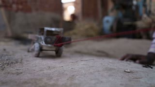Hand pulling truck toy on ground in house in Jodhpur, closeup.