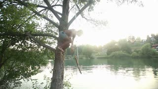 Handsome african american man jumping from a tree into river at sunset, in slow motion