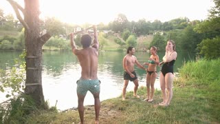 Handsome african american man jumping off rope swing into river while happy friends cheer for him, graded
