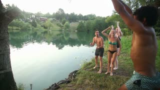 Handsome african american man jumping off rope swing into river while happy friends cheer for him, in slow motion