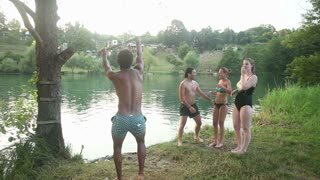 Handsome african american man jumping off rope swing into river while happy friends cheer for him