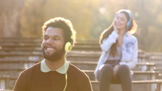 Handsome man and beautiful woman listening to music on headphones at the park, graded