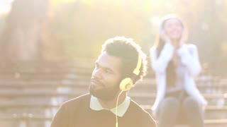 Handsome man and beautiful woman listening to music on headphones at the park, slow motion, graded