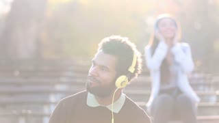 Handsome man and beautiful woman listening to music on headphones at the park, slow motion