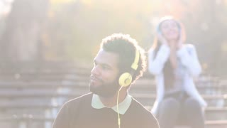 Handsome man and beautiful woman listening to music on headphones at the park
