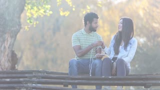 Handsome man and beautiful woman listening to music together, sharing earphones at the park