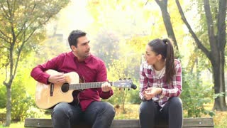 Handsome man playing guitar and singing with beautiful brunette women while sitting on bench in park, graded