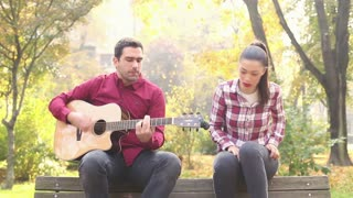 Handsome man playing guitar and singing with beautiful brunette women while sitting on bench in park, in slow motion, graded