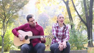 Handsome man playing guitar and singing with beautiful brunette women while sitting on bench in park, in slow motion