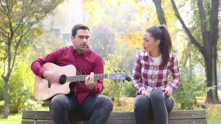 Handsome man playing guitar and singing with beautiful brunette women while sitting on bench in park