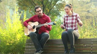 Handsome man playing guitar and singing with beautiful woman while sitting on park bench, graded