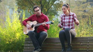 Handsome man playing guitar and singing with beautiful woman while sitting on park bench