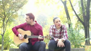 Handsome man playing guitar while beautiful young woman singing in park, graded