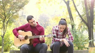 Handsome man playing guitar while beautiful young woman singing in park, in slow motion, graded