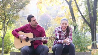 Handsome man playing guitar while beautiful young woman singing in park, in slow motion