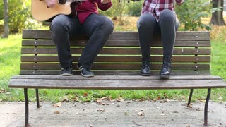 Handsome man playing guitar while beautiful young woman singing in park