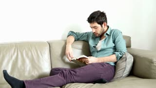Handsome man sitting on comfortable couch reading book