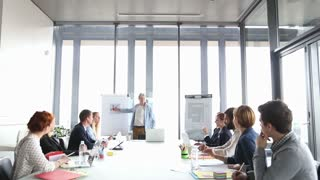 Handsome middle age creative director giving presentation in conference room, pointing at flipchart