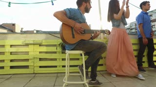 Handsome musician playing guitar, young people dancing at the rooftop party
