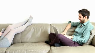 Handsome woman laying on couch speaking to sitting man