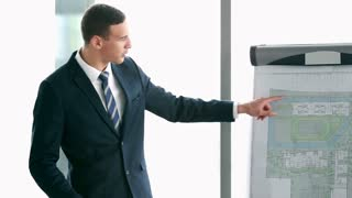 Handsome young businessman pointing at flipchart during presentation in conference room