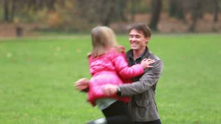 Handsome young dad carries daughter and plays with her in park in autumn