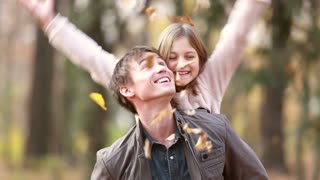 Handsome young father gives daughter piggyback ride while she throws leaves in the air in park