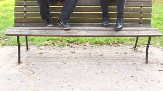 Handsome young man and beautiful women playing guitar and singing while sitting on bench in park, graded