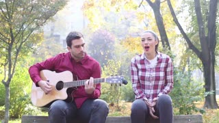 Handsome young man and beautiful women playing guitar and singing while sitting on bench in park