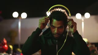Handsome young man dancing to the rhythm of music with headphones in amusement park