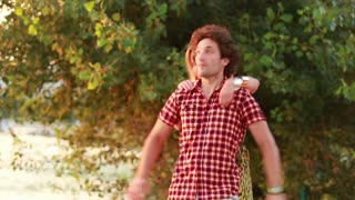 Handsome young man giving his beautiful girlfriend a piggyback ride and laughing.