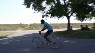Handsome young man having fun cycling with hands in the air