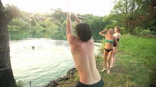 Handsome young man jumping off rope swing into river while happy friends cheer for him, graded, in slow motion