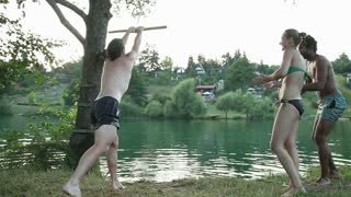 Handsome young man jumping off rope swing into river while happy friends cheer for him, in slow motion
