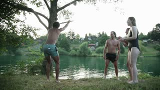 Handsome young man jumping off rope swing into river while happy friends cheer for him