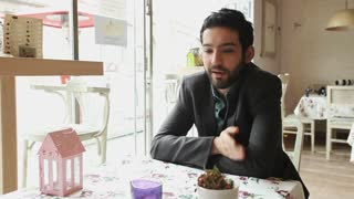 Handsome young man talking in a cafe