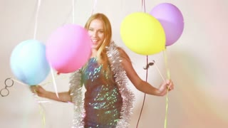 Happy blonde woman jumping with balloons in photo booth