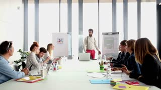 Happy business people clapping after presentation of their colleague in conference room, graded