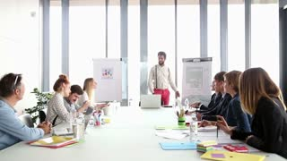 Happy business people clapping after presentation of their colleague in conference room
