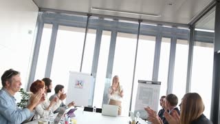 Happy business people clapping during a meeting in conference room