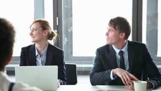 Happy business people sitting at table in conference room and listening presentation of female colleague