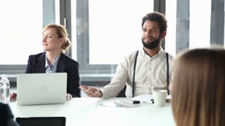 Happy business people sitting at table in conference room and listening presentation