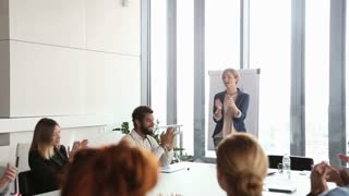 Happy Colleagues applauding after presentation in conference room