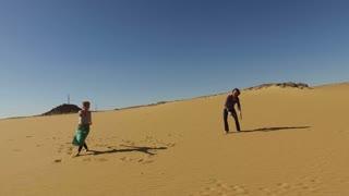 Happy couple dancing barefoot in desert, Egypt