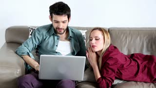 Happy couple on comfortable couch surfing on laptop in living room