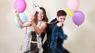 Happy crazy couple enjoying dancing in photo booth