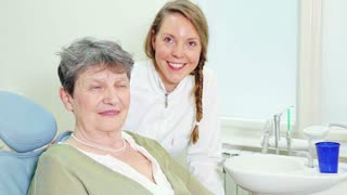 Happy female dentist with patient looking at camera