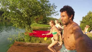 Happy handsome man holding camera while jumping into river with friends, in slow motion
