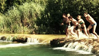 Happy handsome man holding camera while jumping into river with friends, side view, graded