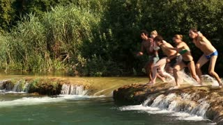 Happy handsome man holding camera while jumping into river with friends, side view
